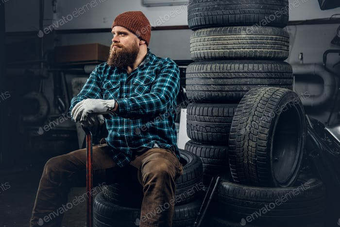 A man sits on a tire.