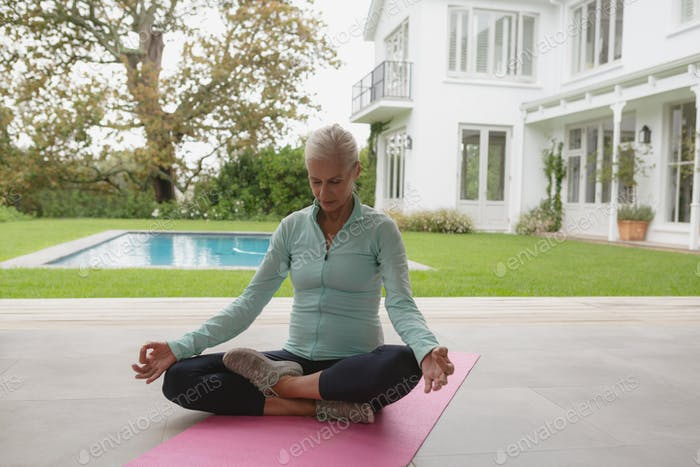 Determined active senior Caucasian woman doing yoga on exercise mat in the porch at home