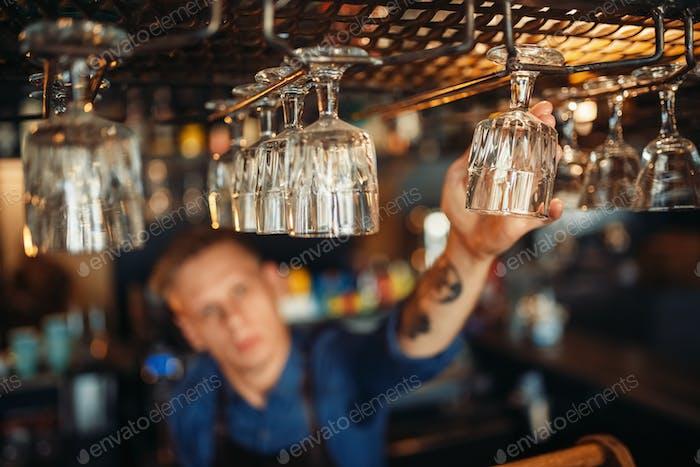 Männlicher Barkeeper nimmt sauberes Glas von Bartheke