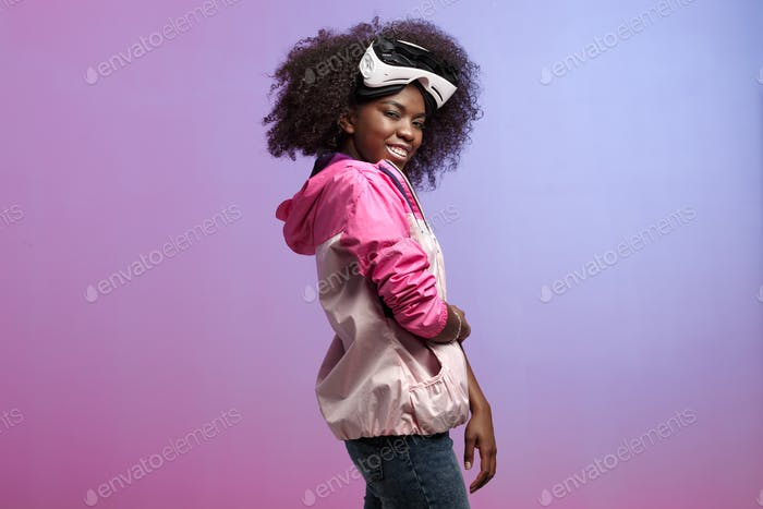 Funny curly brown-haired girl dressed in the pink sports jacket is wearing on her head the virtual