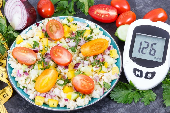 Glucometer with sugar level, salad with vegetables and bulgur groats, tape measure