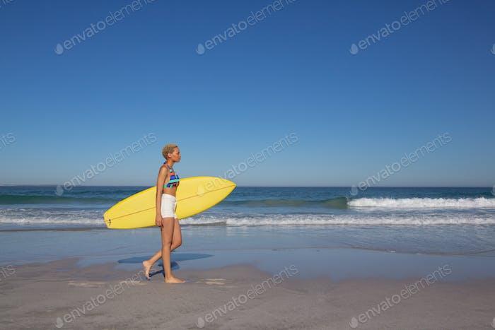 Seitenansicht der Afroamerikanerin im Bikini zu Fuß mit Surfbrett am Strand in der Sonne