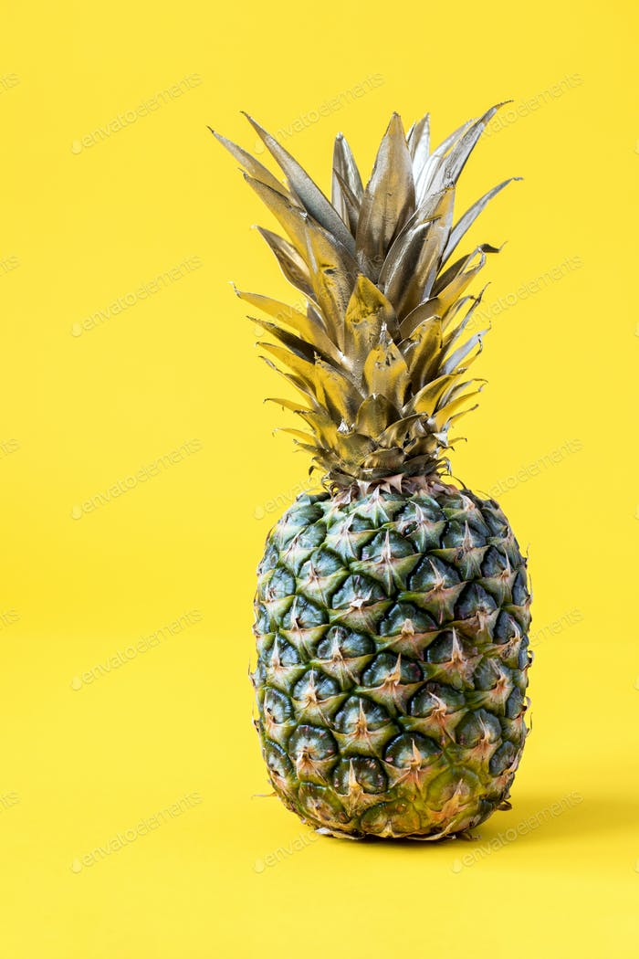 Creative layout made gold pineapple on brightly yellow background.Minimal style.