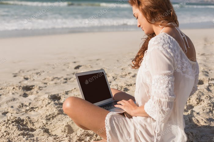 Side view of beautiful young Caucasian woman using laptop sitting on the beach. It is sunny day