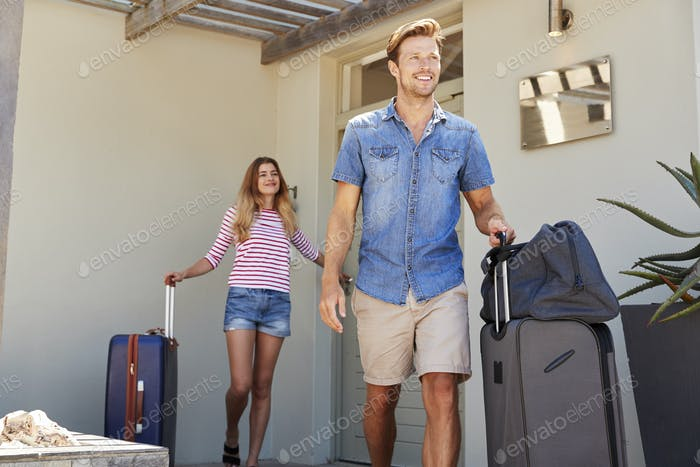 Couple With Luggage Leaving House For Vacation