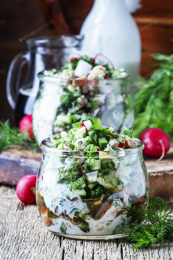 Summer cold soup with vegetables, herbs and yogurt in glass jars