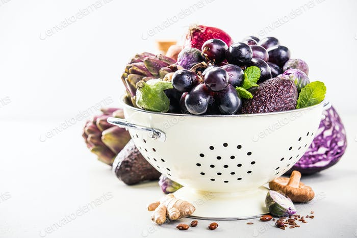 Purple fruits and vegetables in colander - space for text