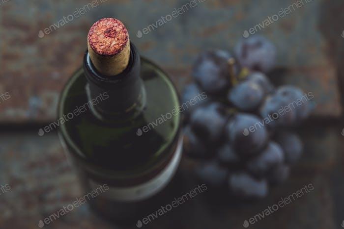Draufsicht der Rotweinflasche. Makroselektiver Fokus auf Weinkork. Weinflasche, Weinglas und Trauben