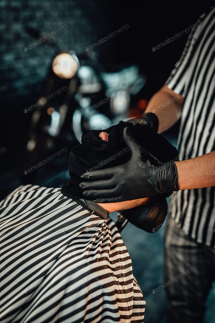 Barber drying his client's hairs with special hat