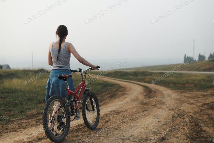 young woman walking with bike on village road