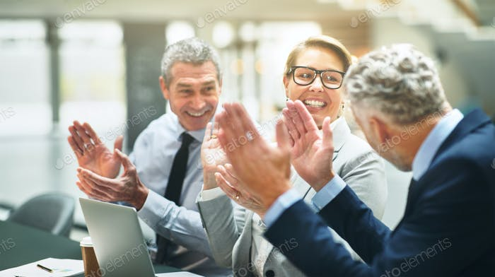 Smiling mature businesspeople clapping together in an office