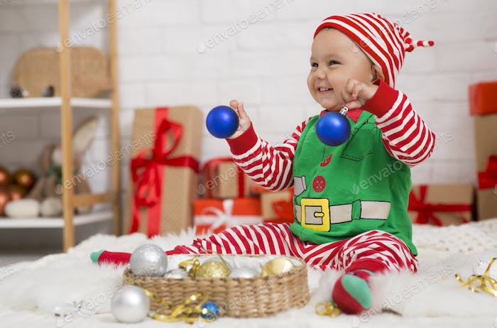 Playful baby elf playing with Xmas decorations