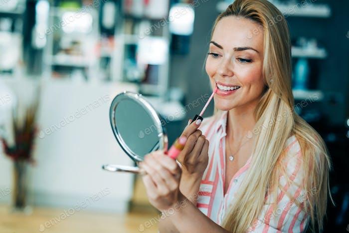 Young beautiful woman applying make up using small mirror