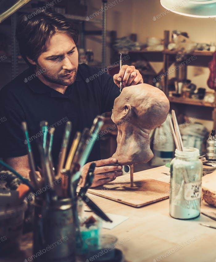 Mann, der in einem prothetischen speziellen FX-Workshop arbeitet