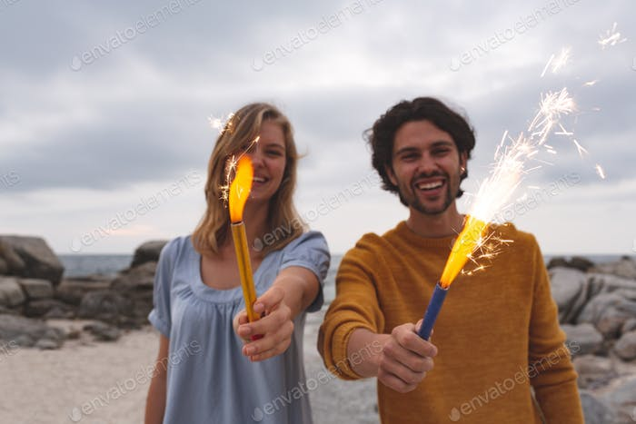 Young couple playing with fire cracker while standing at beach