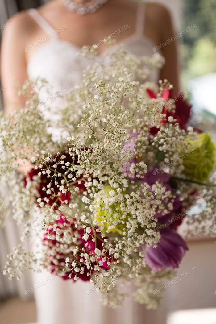 Midsection of bride holding bouquet at home
