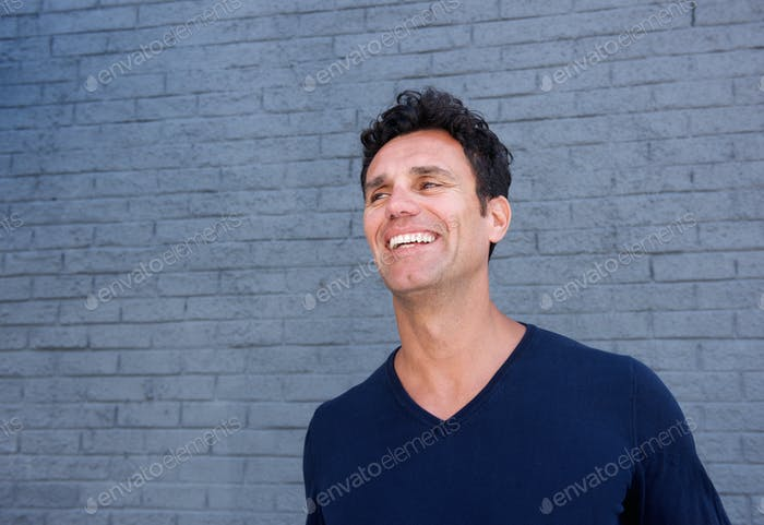 Handsome mature man smiling against gray wall