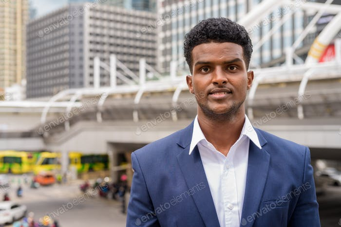 Portrait of African businessman looking at camera while in city