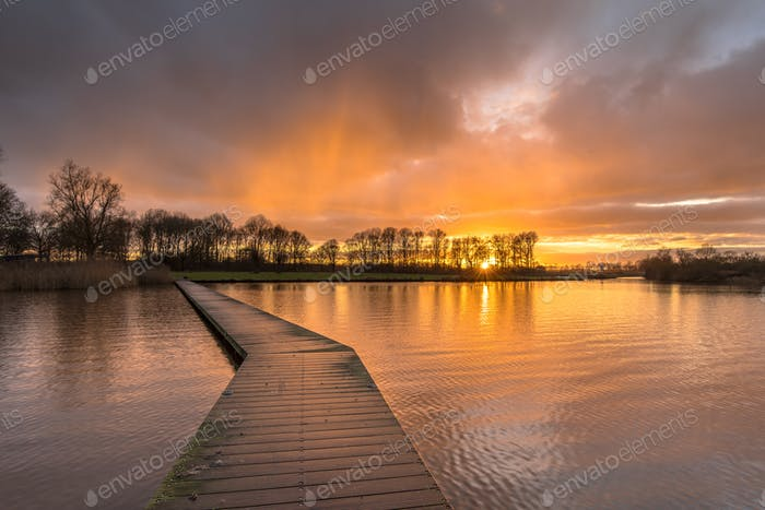 Wooden walkway in lake under orange sunset