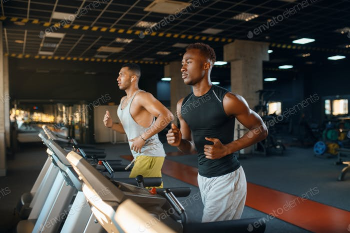 Two athletes runs on treadmill, training in gym