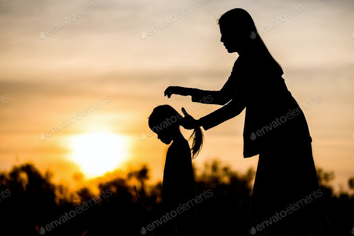 Silhouetted of mother tied hair to daughter