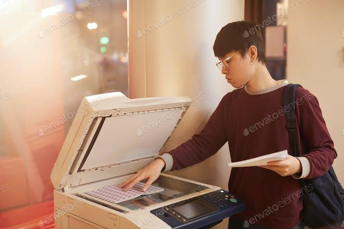 Asian student using printer