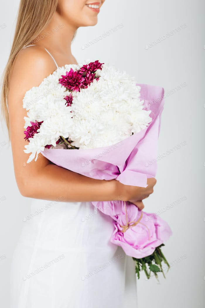 Close-up delicate woman hands holding bunch of flowers