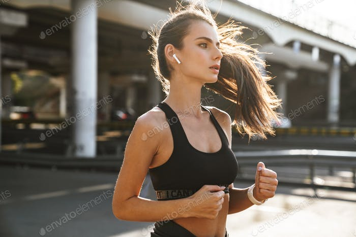 Concentrated young woman running outdoors