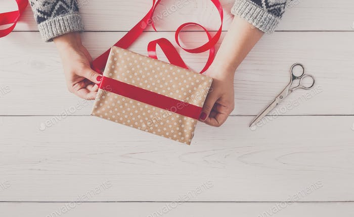 Woman's hands wrapping christmas holiday present with red ribbon