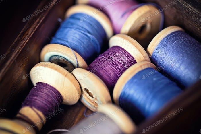 Collection of blue spools threads  arranged in a grunge wooden box