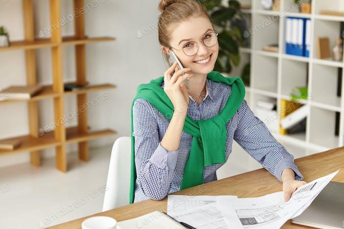 Menschen, Konzept der Geschäftsgespräche. Fröhliche junge Managerin unterhält sich über smart pho