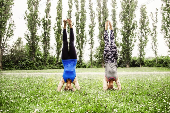 Women doing supported headstands at park