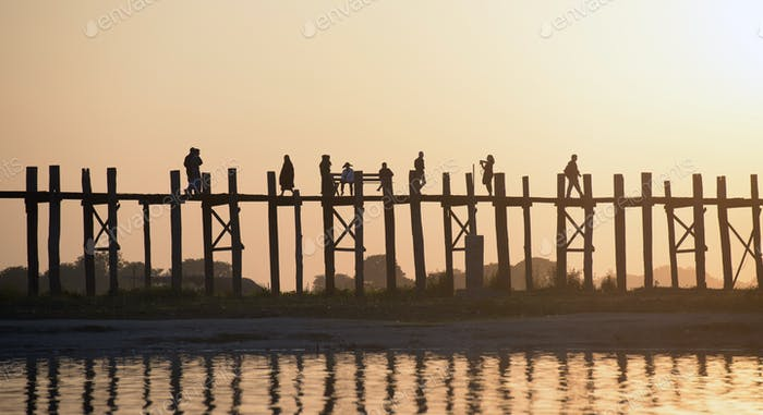 People walking on elevated wooden walkway at sunset