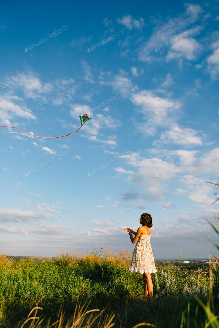 Girl playing with kite in field