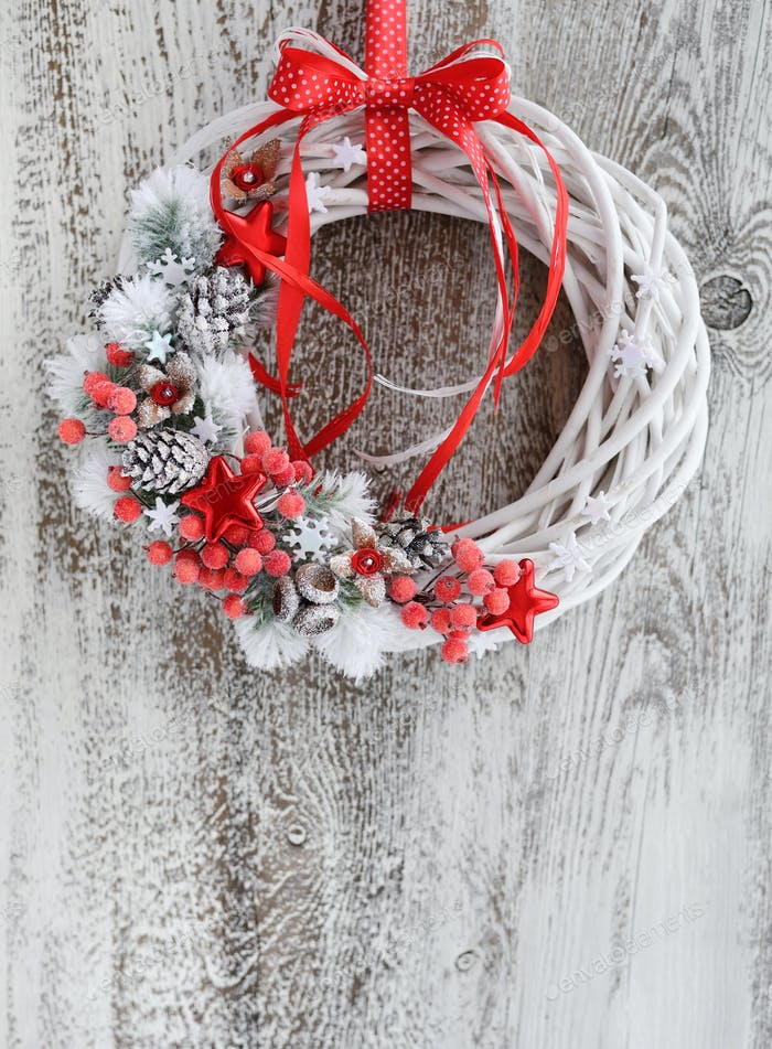 Christmas wreath with red ribbon on a vintage wooden background.