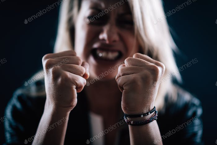 Aggression – Portrait of an Angry Aggressive Woman with Clenched Fists