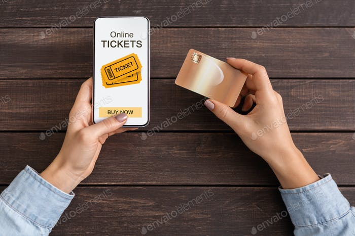 Woman buying event tickets via app on smartphone and credit card