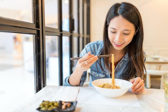 Frau essen Nudeln im chinesischen Restaurant