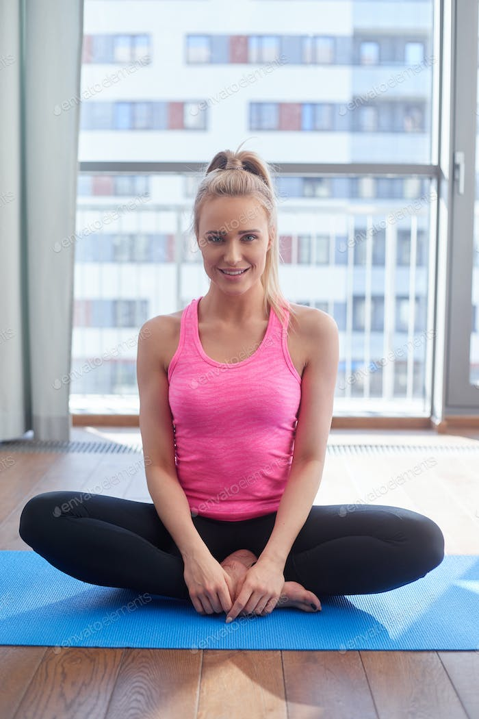 Attractive young blonde woman exercising and sitting in yoga lotus position