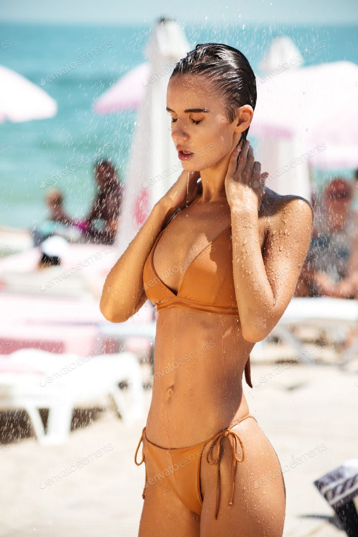 Pensive girl in beige bikini dreamily closing her eyes taking shower on beach