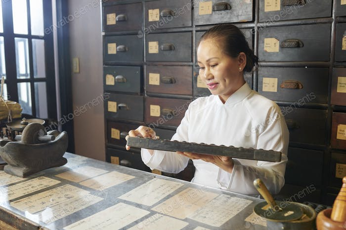 Vietnamese woman working at traditional apothecary