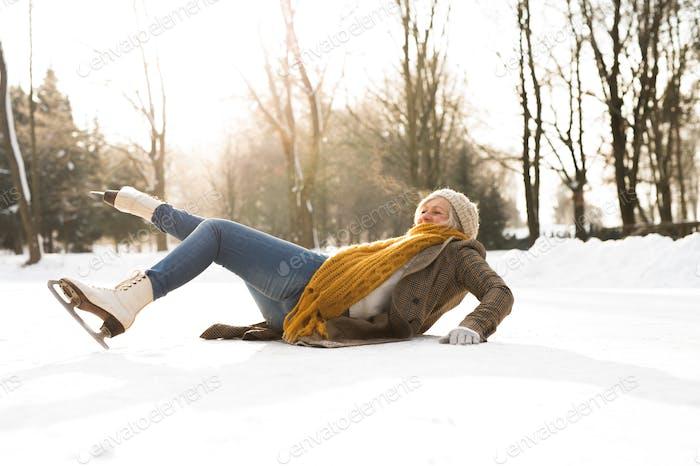 Senior Frau auf dem Eis nach einem Sturz.