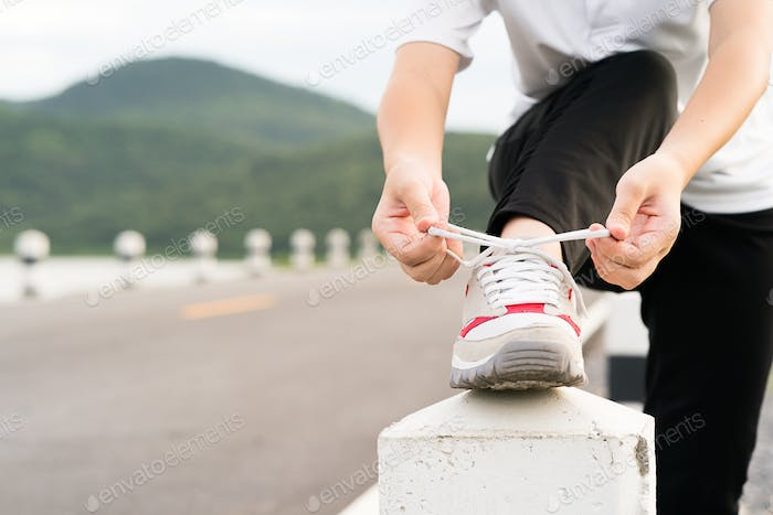 Woman tying shoelace his before starting running-2