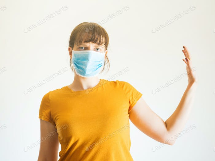 Young woman in face mask with raised arm