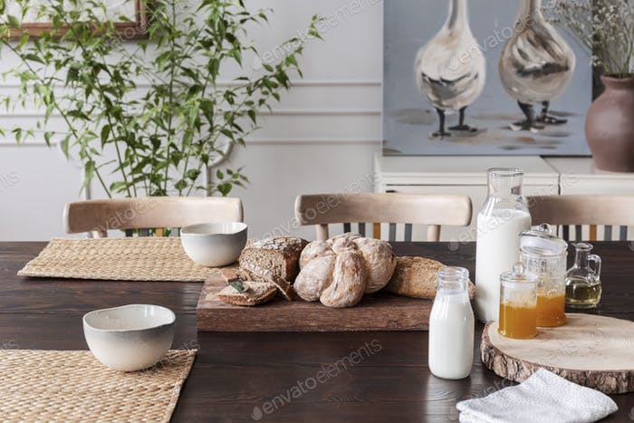 Milk, natural honey and bread on cottage wooden table in dining