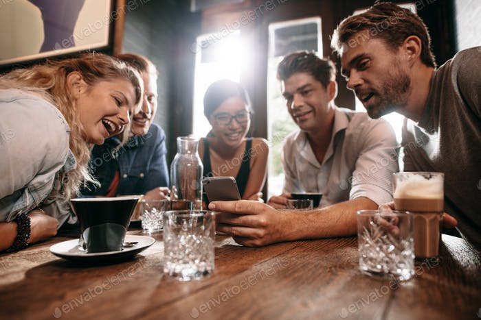Friends looking at mobile phone while sitting in cafe