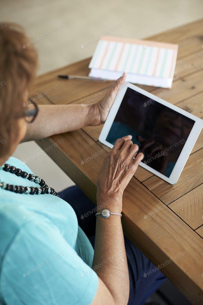 Senior Frau sitzt am Tisch mit Tablet-Computer, erhöhte Schulteransicht, vertikal