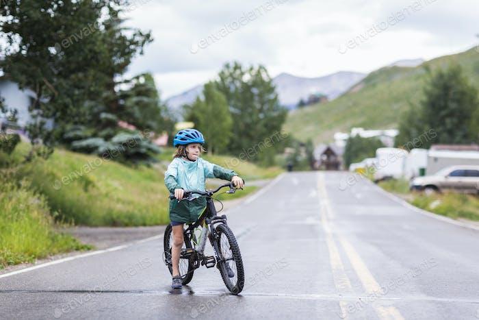 5 year old boy straddling his mountain bike on rainy road