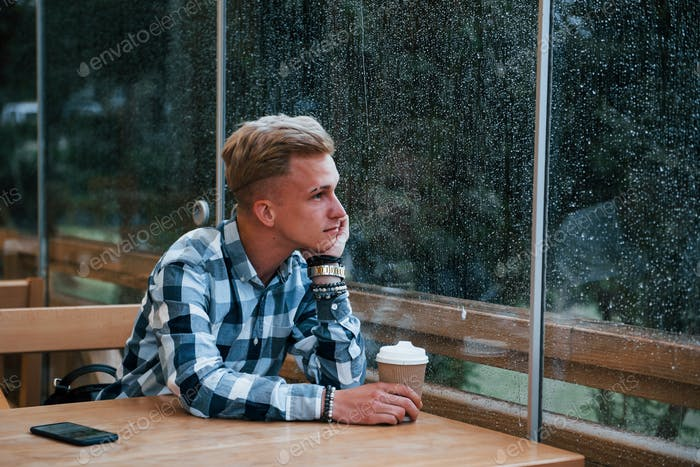 Portrait of young student that sits in cafe at rainy day. One person