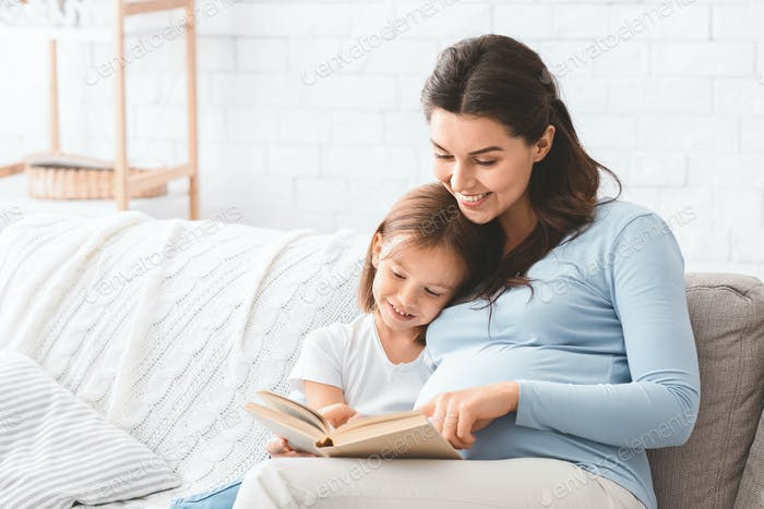 Lovely little girl reading book with her pregnant mom